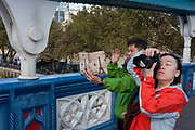 Tourists stop to take photos by one of Tower Bridges giant Victorian-designed suspension chains, on 6th October 2016, in London, England. The bridge is undergoing repairs, closed to traffic and disrupting this major Thames crossing and surrounding roads for the next three months. Closed for repairs to traffic and disrupting this major Thames crossing and surrounding roads for the next three months.