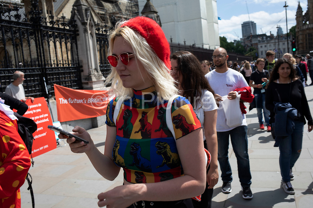 Young woman wearing a dinosaur print multicoloured t-shirt and red beret in London, England, United Kingdom.