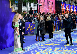 Guy Ritchie and Jacqui Ritchie (left) pose for a photographer whilst attending the Aladdin European Premiere held at the Odeon Luxe Leicester Square, London.