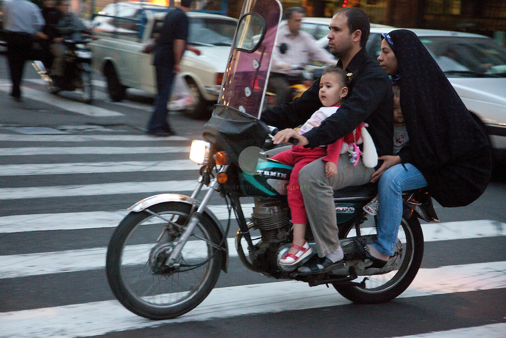 The roads of Tehran are a dangerous territory. Every driver follows his own rules.  And while driving in a car in Tehran is already nerve-wracking, there is a progression to this: to maneuver the streets by motorcycle - a life and death experience. Motorcyclist are taking advantage of the full space - including the sidewalks. Usage of helmets seems not to be a widespread practice. However, for women the wear of the abaya - or at least of a headdress - is compulsory.