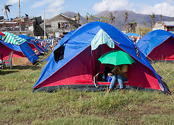 26/11/2013.  A woman takes shelter from the sun under an umbrella outside one of the many tented sites that are now home to those whose houses were destroyed by a super typhoon in the city of Tacloban in the Philippines.  Photo credit: Alison Baskerville/LNP