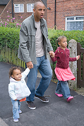 Father walking with his young daughters in the street,