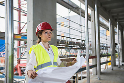 Female architect with blueprint at construction site, Munich, Bavaria, Germany