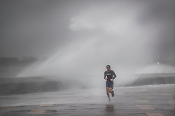 © Licensed to London News Pictures. 09/02/2020. Portsmouth, UK. A runner braves high tide on the sea front at Southsea, Portsmouth as Storm Ciara batters the UK. Airlines have cancelled dozens of domestic and international flights as the storm brings strong winds and rain. Photo credit: Peter Macdiarmid/LNP
