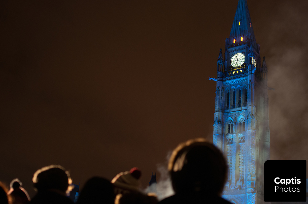 Smoke rises past the Peace Tower as people warm up near a fire. December 3, 2014.