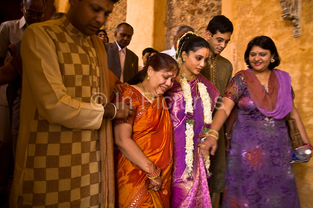 At a Hindu wedding the newly wed bride, Shweta Singhal  (centre) supports her sobbing mother on one side and brother on the other as she and her husband, Rohit, leave the wedding ceremony after its climatic conclusion  to begin a new life, Neemrana Fort Palace, Rajasthan, India