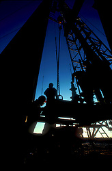 Men working on an onshore oil rig work site at dusk.