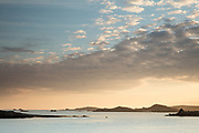 Dawn hues reflect in calm morning waters, amidst the isles and islets of the Isles of Scilly. As seen from Old Grimsby Harbour, Tresco. UK.