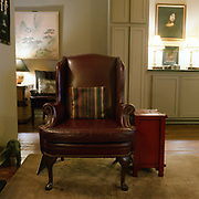 A redish leather chair, very classic looking, with a small stripped pillow on it, on a non-descript carpet, in a darkened room with an Asian landscape in the left background and a portrait of a woman on the right background.