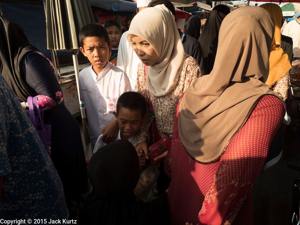 18 JUNE 2015 - PATTANI, PATTANI, THAILAND:   Women in the Pattani Ramadan Bazaar, a sprawling street food market that is open during Ramadan. People come to the street food market late in the day to buy meals for the evening Iftar meal, which breaks the day long fast. Ramadan is the ninth month of the Islamic calendar, and is observed by Muslims worldwide as a month of fasting to commemorate the first revelation of the Quran to Muhammad according to Islamic belief. This annual observance is regarded as one of the Five Pillars of Islam. Islam is the second largest religion in Thailand. Pattani, along with Narathiwat and Yala provinces, all on the Malaysian border, have a Muslim majority.       PHOTO BY JACK KURTZ