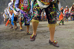Line of male dancers in traditional embroidered clothing (legs only), Pentecostes Festival held annually in May, Ollantaytambo, Peru, South America
