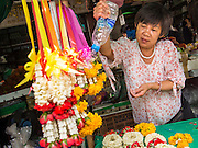 "23 AUGUST 2013 - BANGKOK, THAILAND:    A vendor waters flower garlands she is selling in Pak Khlong Talad, the flower market in Bangkok. Thailand entered a ""technical"" recession this month after the economy shrank by 0.3% in the second quarter of the year. The 0.3% contraction in gross domestic product between April and June followed a previous fall of 1.7% during the first quarter of 2013. The contraction is being blamed on a drop in demand for exports, a drop in domestic demand and a loss of consumer confidence. At the same time, the value of the Thai Baht against the US Dollar has dropped significantly, from a high of about 28Baht to $1 in April to 32THB to 1USD in August.    PHOTO BY JACK KURTZ"