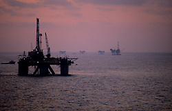 Stock photo of a semi-submersible offshore drilling rig operating at sunset