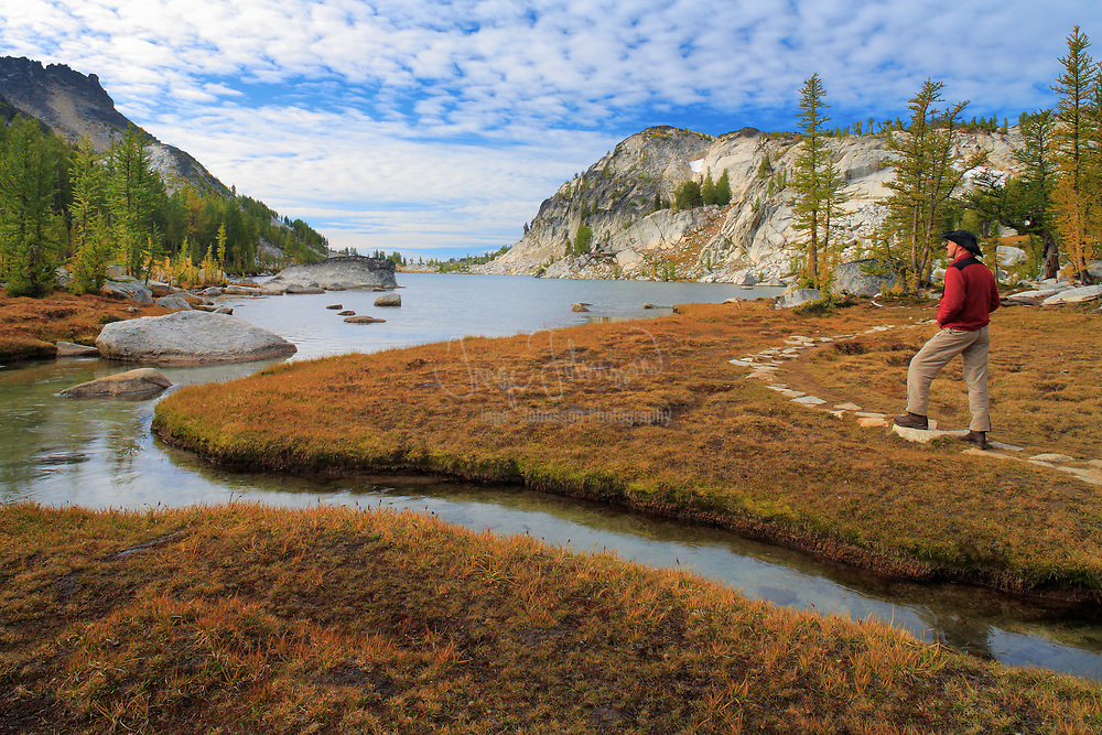 Hiker walking near creek at Perfection Lake in the Enchantment Lakes area of Alpine Lakes Wilderness, Washington