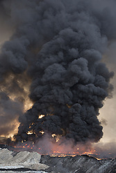 October 21, 2016 - Qayyarah, Iraqi-Kurdistan, Iraq - Smoke rises from burning oil wells, now on fire for around two months, in the town of Qayyarah, Iraq. The oil wells, located in a residential neighbourhood on the edge of the town, were set alight in July by retreating Islamic State militants as part of a scorched earth policy...Since being retaken from the Islamic State the town of Qayyarah has become an important staging post for the Iraqi Army, and some US support elements, in the buildup to the Mosul offensive. (Credit Image: © Matt Cetti-Roberts/London News Pictures via ZUMA Wire)