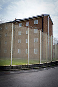 Security fencing around HMP Coldingley. Surrey, United Kingdom. HMP Coldingley is a category C training prison and was built in 1969. Coldingley is focussed on the resettlement of prisoners, and all inmates must work a full working week, within the prison grounds.