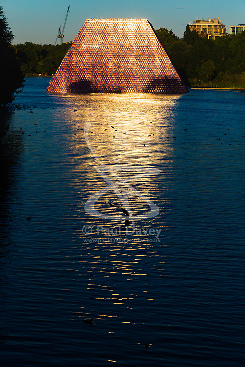 Shimmering in the evening sunshine and reflected on the water is artist Christo's 'Mastaba', an installation made up of over 7,000 barrels floating on The Serpentine in London's Hyde Pak. London, July 02 2018.