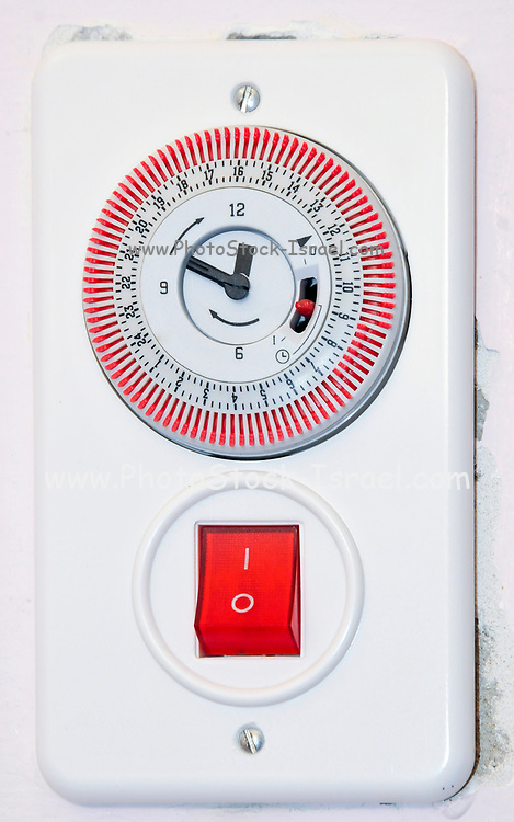 Hot water boiler switch with timer and red pilot light on a wall