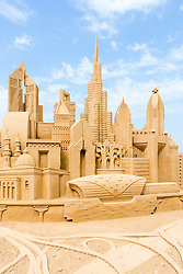 Sand sculpture of skyline of Dubai with many landmark buildings on beach in Dubai United Arab Emirates