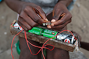 A boy plays with batteries and a small light in the West Point slum in Monrovia, Montserrado county, Liberia on Monday April 2, 2012.