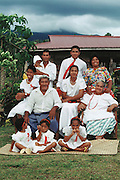 The Lagavale family, dressed in their Sunday best for the White Sunday holiday church services, cheerfully pose for the camera in Western Samoa. White Sunday (also called Children's Day) is celebrated on the second Sunday of October each year. In this tradition brought to the island by the London Missionary Society, the children receive new clothes and gifts, and festive games are played. The Lagavale family lives in a 720-square-foot tin-roofed open-air house with a detached cookhouse in Poutasi Village, Western Samoa. Material World Project.