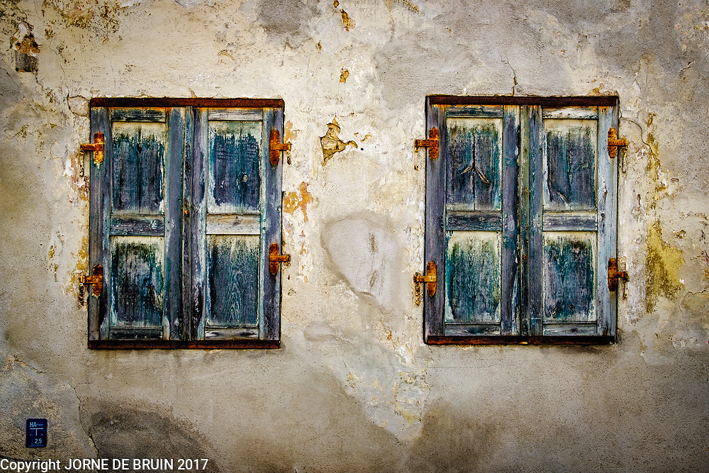 Weathered shutters with rusted hinges on an old wall in a german town.