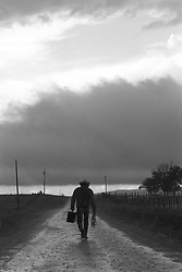 cowboy carrying a suitcase walking on a dirt road in a rain storm