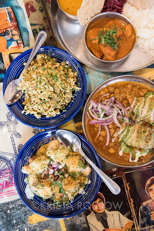 An assortment of Indian dishes includes bhel puri, samosa chat, dehi sev papdi, and a chicken thali plate at Chai Pani, an Indian street food restaurant located at 22 Battery Park Avenue in Downtown Asheville, North Carolina.