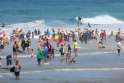 © Licensed to London News Pictures. 01/08/2019. Perranporth, UK. Beachgoers enjoy the sea during warm weather on one of the busiest days of the year at  Perranporth beach, Cornwall. The weather in the south west is set to stay warm over the weekend, after a rainy start to the week. Photo credit : Tom Nicholson/LNP