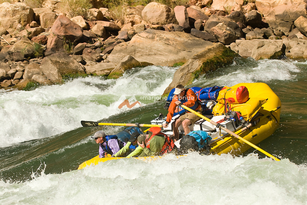 Passengers duck while running the Roaring Twenties, rafting the Colorado River in the Grand Canyon National Park, Arizona.