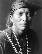 Head-and-shoulders portrait of Navajo man, facing slightly right, wearing headband and silver squash blossom necklace.1906. Photograph by Edward Curtis (1868-1952).