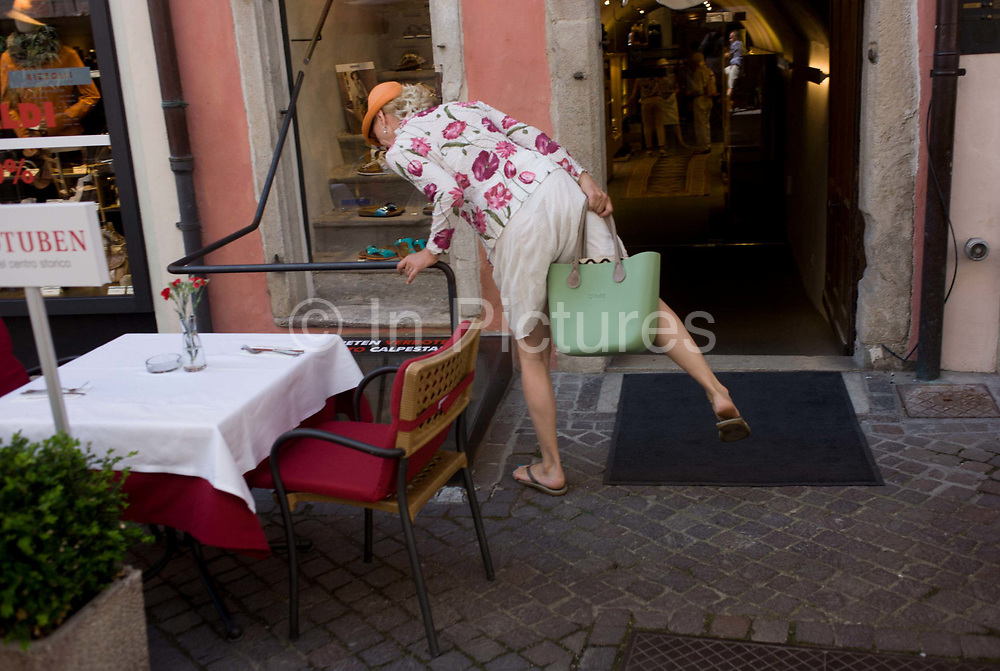 A lady shopper stretches to see down a lower-level floor in the northern Italian south Tyrolean city of Bozen-Bolzano. Seemingly falling over into the hole where supplies are lowered into the basement, the lady balances on one leg and holds her bag to steady herself.
