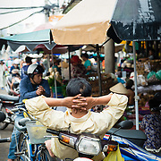 Motor bike driver resting on bike at market in Saigon