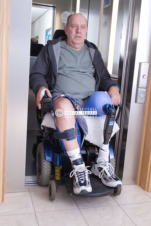 Male wheelchair user coming out of a lift at his local sports leisure centre,