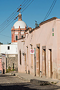 The dome of the Parroquia de San Pedro Apóstol church or Saint Paul the Apostle provincial church and cobblestone street in Mineral de Pozos, Guanajuato, Mexico. The town, once a major silver mining center was abandoned and left to ruin but has slowly comeback to life as a bohemian arts community.