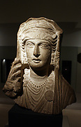 Limestone bust.  A veiled woman wearing an elaborate head-band, earrings and necklace of beads.  From a sculpture set in a tomb at Palmyra, Syria, about AD 80-120. The woman's hairstyle mimics Roman imperial portraits of the age of Claudius and Nero (AD41-68), but the lavish jewellery is typical of the turn of the century.