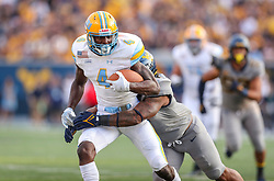Sep 11, 2021; Morgantown, West Virginia, USA; Long Island Sharks wide receiver Derick Eugene (4) makes a catch and is tackled by West Virginia Mountaineers linebacker Josh Chandler-Semedo (7) during the second quarter at Mountaineer Field at Milan Puskar Stadium. Mandatory Credit: Ben Queen-USA TODAY Sports