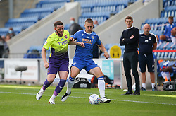 Luke Norris of Colchester United and Pierce Sweeney of Exeter City tussle for the ball as the managers look on - Mandatory by-line: Arron Gent/JMP - 18/06/2020 - FOOTBALL - JobServe Community Stadium - Colchester, England - Colchester United v Exeter City - Sky Bet League Two Play-off 1st Leg