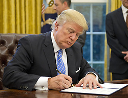 January 23, 2017 - Washington, District of Columbia, U.S. - President DONALD TRUMP signs the last of three Executive Orders in the Oval Office of the White House. The three executive orders, signed Monday at the White House, include formally withdrawing the U.S. from the Trans-Pacific Partnership (TPP)  trade deal, implementing a federal employee hiring freeze, and reinstate a GOP-backed policy regarding foreign aid and abortion funding. (Credit Image: © Ron Sachs/CNP via ZUMA Wire)
