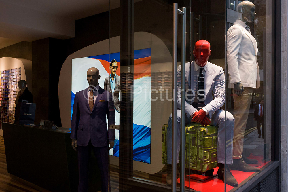 Mannequins displaying casual stylish menswear in the window of City of London branch of the Dutch menswear business Suit Supply. Four of the models stand and sit on full display to passing trade in the side street in the capital's financial district near Leadenhall Market where businessmen in the insurance services work.