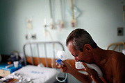 A tuberculosis patient coughs as he holds an oxygen mask inside the male patients' ward at Santa Maria Hospital in Taquara.
