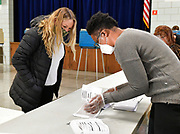 Election judge Addie Lincoln (right) looks up the registration information for voter Katherine Brabenec of Belleville at Douglas School in Belleville, the polling place for precincts 24 and 25 on Tuesday, November 3, 2020.  <br /> Photo by Tim Vizer