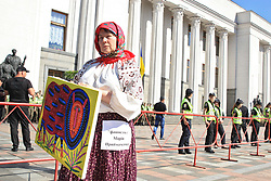 July 5, 2018 - Kyiv, Ukraine - An activist represents Ukrainian folk art painter Maria Pryimachenko during a rally calling to dismiss members of the National Council of Television and Radio Broadcasting Olha Herasymiuk and Oleh Chernysh outside the parliament building, Kyiv, capital of Ukraine, July 5, 2018. Demonstrators believe that the absence of these Council members from meetings for a month and a half impedes the investigation of what they think are the violations by TV channels, including Inter. Ukrinform. (Credit Image: © Nazar Furyk/Ukrinform via ZUMA Wire)