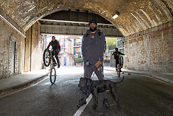 Mac Ferrari and his dog Xuki with riders Liam Ross, 17, left and Trizzy, 16. Bikestormz is the brainchild of leader Mac Ferrari, a group of young trick cyclists who are encouraged to put knives down and enjoy the healthy, positive side of urban youth culture by joining together  and developing their cycling skills. . London, September 27 2019.