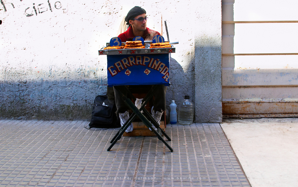 A street merchant with a small stall sitting on the pavement selling candied peanuts Garrapinada Montevideo, Uruguay, South America