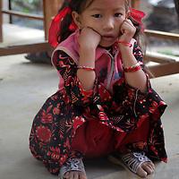Asia, Nepal, Kathmandu, Kirtipur. Young girl sitting on step in village of Kirtipur.