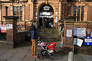 A local mother stops to look at the closed Carnegie Library in Herne Hill, south London while occupiers remain inside the premises on day 6 of its occupation, 5th April 2016. The angry local community in the south London borough have occupied their important resource for learning and social hub for the weekend. After a long campaign by locals, Lambeth have gone ahead and closed the library's doors for the last time because they say, cuts to their budget mean millions must be saved.
