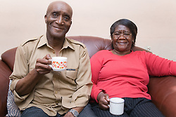 Older couple sitting at home enjoying a cup of coffee,