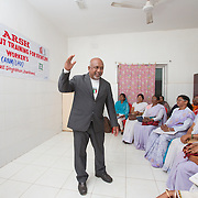 CAPTION: This is a training of frontline workers (FLWs): auxiliary nurse midwives (ANMs) and lady health visitors (LHVs). The latter supervise ANMs. Across the state, there are more than 2,000 FLWs. The Government-approved plan states that these individuals must have five days of training on adolescent reproductive and sexual health matters. It is being conducted by Dr Jagannath Hembrom, a 'Master Trainer'. His role is more as a facilitator than a teacher. There is a pool of 67 such master trainers in Jharkhand, and Dr Jagannath is recognized as one of the best of these.  LOCATION: Ghatshila Community Health Centre (CHC), Purbi Singhbhum (district), Jharkhand (state), India. INDIVIDUAL(S) PHOTOGRAPHED: Left: Dr Jagannath Hembrom; right: multiple people.
