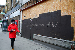© Licensed to London News Pictures. 15/01/2021. London, UK. A woman wearing a protective face covering walks past <br /> graffiti written on a boarded shop front in north London during Coivd-19 lockdown. Supreme court has ruled on a test case by The Financial Conduct Authority (FCA) that hundreds of thousands of small businesses that were forced to close during the first national Covid-19 lockdown will receive insurance payouts on their insurance claims. Photo credit: Dinendra Haria/LNP